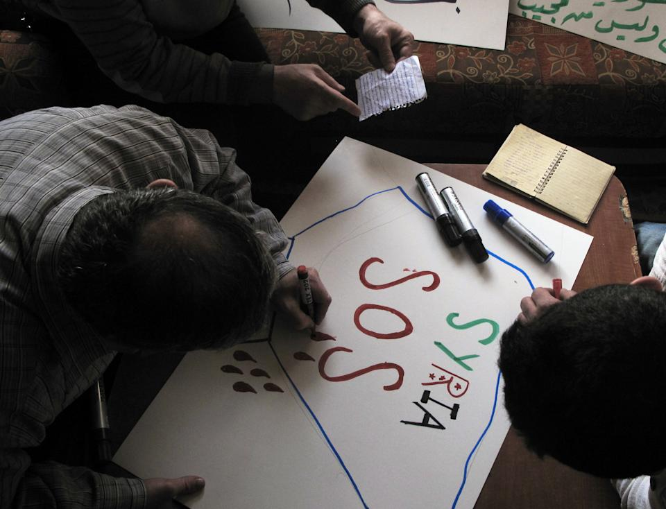 In this Tuesday, April 3, 2012 photo, Syrian activists prepare signs for upcoming protests at a house in a neighborhood in Damascus, Syria. Syrian activists say there have been explosions and clashes in several parts of the country even as the government claims it has started to withdraw troops from some cities in compliance with an international cease-fire plan. (AP Photo)