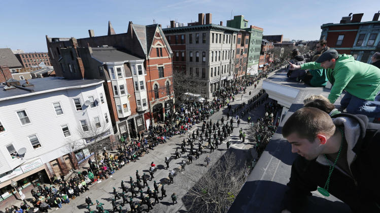 People watch the annual St. Patrick's Day parade from a roof in the South Boston neighborhood of Boston, Sunday, March 16, 2014. (AP Photo/Michael Dwyer)