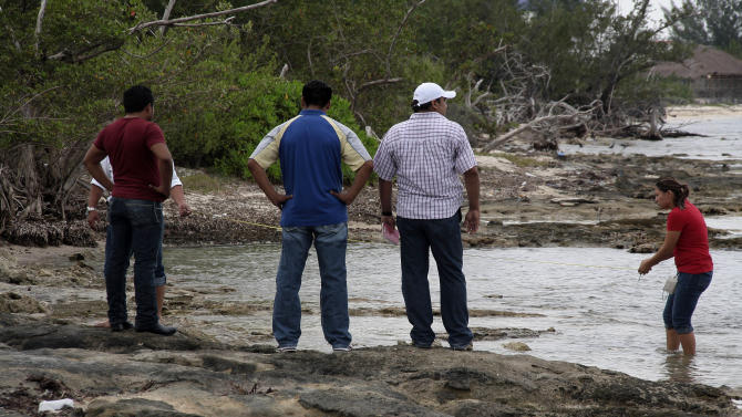 State police investigators and forensic workers examine the scene where a crew member of a Royal Caribbean cruise ship was found dead in the resort island of Cozumel, Mexico, Saturday Feb. 5, 2011. The body of Monika Markiewicz, 32, was recovered from the ocean off the southern part of the island and an autopsy determined the cause of death was drowning but added that Markiewicz also suffered a blow to the head. Police are investigating whether her death was a homicide, according to state authorities and company officials.  (AP Photo/Angel Castellanos)