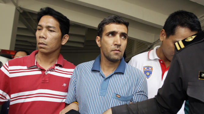 Thai immigration officers escort detained Iranian Mohammad Kharzei, center, at the immigration headquarters in Bangkok on Thursday, Feb. 16, 2012. Kharzei and two fellow Iranians arrested after accidentally setting off an explosives cache in Bangkok were planning to attack Israeli diplomats, Thailand's police chief said Thursday, the first confirmation by local officials that the group was plotting terror attacks in the Southeast Asian country.(AP Photo/Sakchai Lalit)