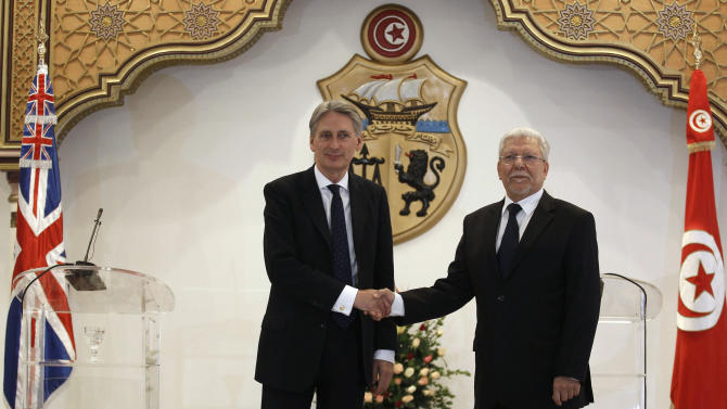 Tunisian FM Baccouche shakes hands with British Foreign Secretary Hammond in Tunis