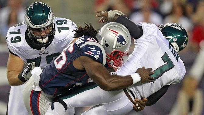 New England Patriots linebacker Jermaine Cunningham (96) drops Philadelphia Eagles quarterback Michael Vick (7) to the field on a hard hit during the first quarter of an NFL preseason football game in Foxborough, Mass., Monday, Aug. 20, 2012.  Vick left the game after the play.  At left is Philadelphia Eagles tackle Todd Herremans. (AP Photo/Steven Senne)