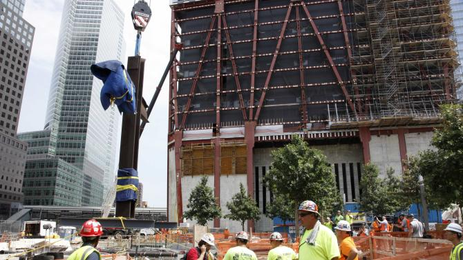 The September 11 cross is lowered by crane into a subterranean section of the National September 11 Memorial and Museum, Saturday, July 23, 2011 in New York. The cross was discovered upright in the ruins of ground zero following the attacks of September 11, 2001. (AP Photo/Mark Lennihan, Pool)