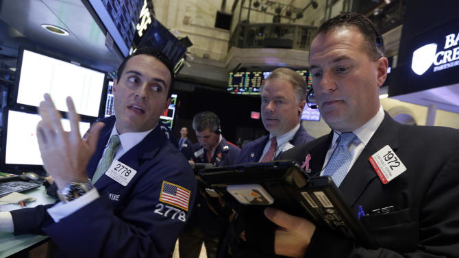 Specialist Michael Gagliano, left, works with traders on the floor of the New York Stock Exchange, Wednesday, Oct. 29, 2014. Major stock indexes traded in a tight range in the early going as investors wait for word from the Federal Reserve and mull over a mixed batch of earnings results. (AP Photo/Richard Drew)