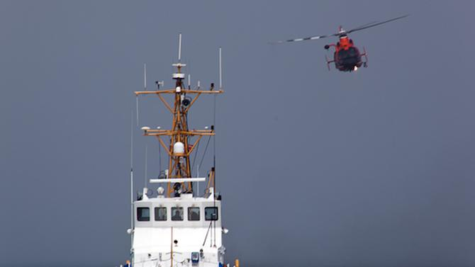 CORRECTS DATE OF CRASH TO SUNDAY, NOT MONDAY - In this Aug. 29, 2011 photo provided by the U.S. Coast Guard, a Rescue Helicopter from Airs Station Los Angeles conducts a close fly-by of the Coast Guard Cutter Halibut. A smuggler's vessel rammed a small U.S. Coast Guard boat deployed by the cutter Halibut, off the Southern California coast early Sunday Dec. 2, 2012, killing one Coast Guard member and injuring another, authorities said. The cutter was conducting an investigation into suspected smuggling near the Channel Islands west of Malibu. (AP Photo/U.S. Coast Guard/Steve Lee)