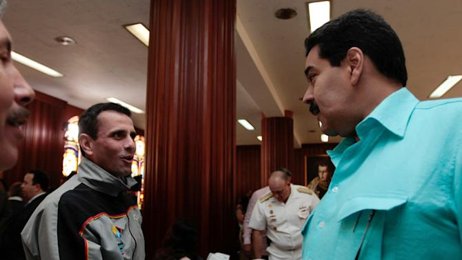 In this photo released by Miraflores Press Office, Venezuela's Vice President Nicolas Maduro, right, shakes hand with opposition leader, Miranda state Gov. Henrique Capriles during a meeting with the country's state governors, in Caracas, Venezuela, Tuesday, Jan. 15, 2013. Maduro said in a televised meeting with state governors that President Hugo Chavez has been making progress in his treatment for a severe respiratory infection and asked questions of his aides during a visit in Cuba. (AP Photo/Miraflores Press Office)