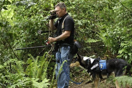 U.S. Army Spc. Mike Ballard stands with Apollo, his service dog, during an archery shooting session, Friday, May 17, 2012, in Puyallup, Wash. Ballard says his dog helps him get through the worst symptoms of the post-traumatic stress disorder that is a remnant of an explosion in Afghanistan that ended his career as an Army medic. (AP Photo/Ted S. Warren)