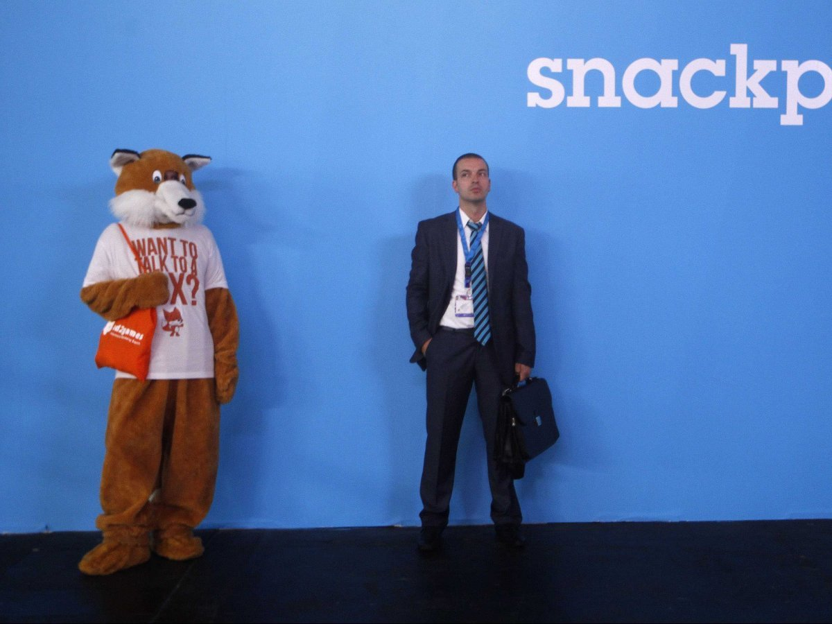 A man and a fox stand against a wall