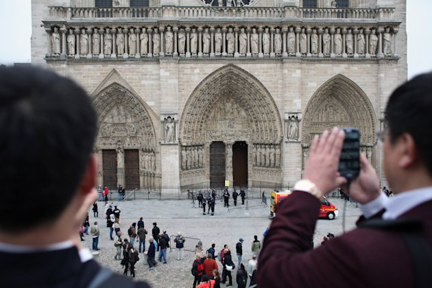 Tourists take pictures as police officers stand guard in front of Notre Dame Cathedral, in Paris, Tuesday, May 21, 2013. Notre Dame has been evacuated after a man committed suicide in the 850-year-old