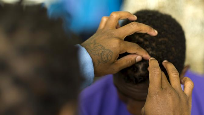 """Inmate Dominic LeBlue does hair of his son Damien during special Father's Day visit part of the """"Get On The Bus"""" program at California Men's Colony in San Luis Obispo"""