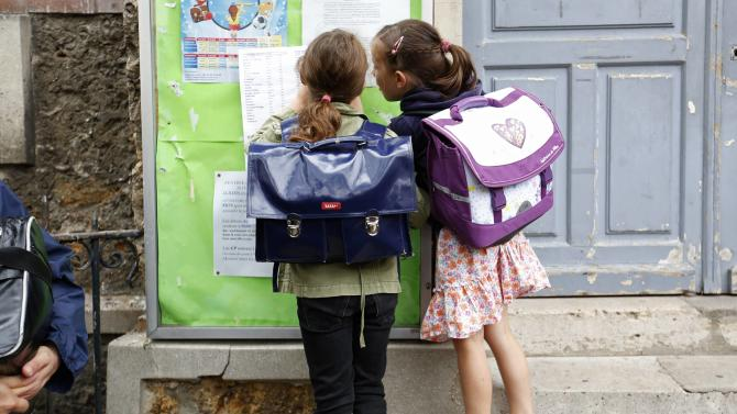 Schoolchildren check a class list before entering the primary school Jules Ferry in Fontenay-sous-Bois near Paris, on the start of the new school year in France