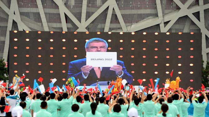 People cheer as they watch on a screen the IOC announcing Beijing as the winner city for the 2022 winter Olympics bid, outside the Birds' Nest, also known as the National Stadium, in Beijing