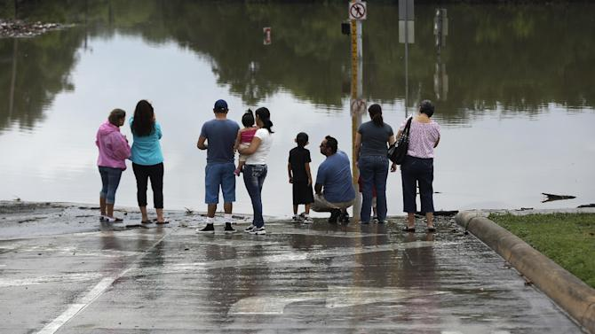 FILE - In this Sunday, May 26, 2013 file photo, onlookers gather along a flooded intersection in San Antonio. On Wednesday, Jan. 14, 2014, scientists from National Oceanic and Atmospheric Administration say 2013 was the wettest year for the continental U.S. since 2009. The average rainfall totaled 31 inches, 2 inches above the previous century's average. (AP Photo/Eric Gay)