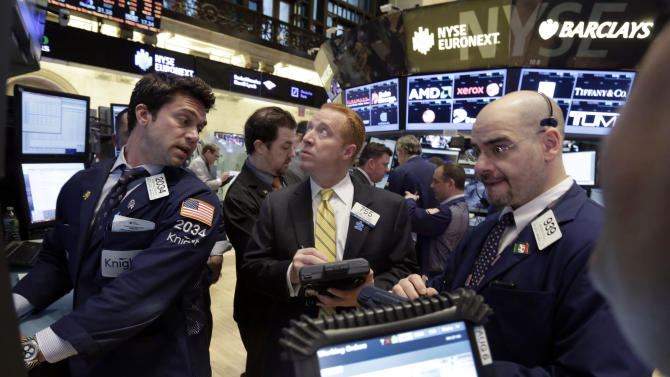 In this March 19. 2013, photo, specialist Joseph Dreyer, left, works with traders on the floor of the New York Stock Exchange. World stock markets stalled Thursday March 21, 2013 as uncertainty mounted over whether Cyprus can stave off bankruptcy after the country's government rejected a plan to contribute to a bailout by seizing money from people's bank accounts. (AP Photo/Richard Drew)