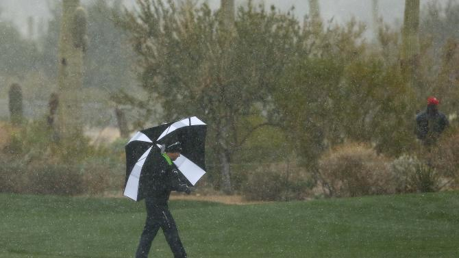 Hunter Mahan makes his way along the 10th fairway as snow and rain fall during the Match Play Championship golf tournament, Tuesday, Feb. 19, 2013, in Marana, Ariz. Play was suspended. (AP Photo/Ross Franklin)