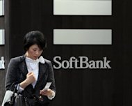 A woman uses her mobile phone outside a Softbank mobile phone shop in Tokyo. Japanese mobile carrier Softbank is eyeing a multi-billion dollar entry into the US telecoms market through the purchase of Sprint Nextel, possibly vaulting it among the top three mobile firms globally