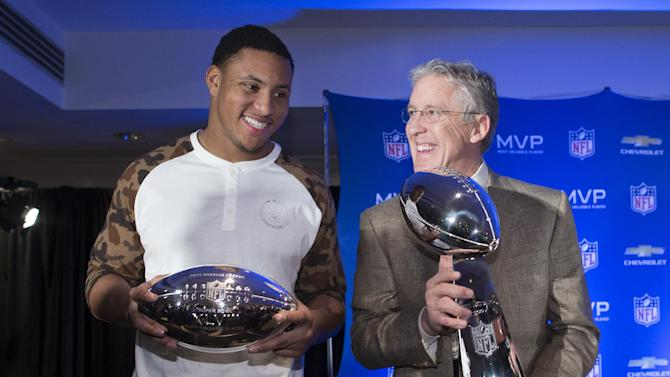 Seattle Seahawks head coach Pete Carroll, right, poses for a photograph with the Vince Lombardi trophy alongside Super Bowl XLVIII MVP Malcolm Smith, during a news conference at the Super Bowl Media Center at the Sheraton hotel, Monday, Feb. 3, 2014, in New York. The Seattle Seahawks defeated the Denver Broncos, 43-8. (AP Photo/John Minchillo)