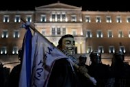 Protesters demonstrate outside the Greek parliament against the new austerity measures in Athens. The Greek parliament on Sunday approved a slashed 2013 budget which the government has vowed will secure the release of foreign aid vital to save the debt-ridden country from insolvency