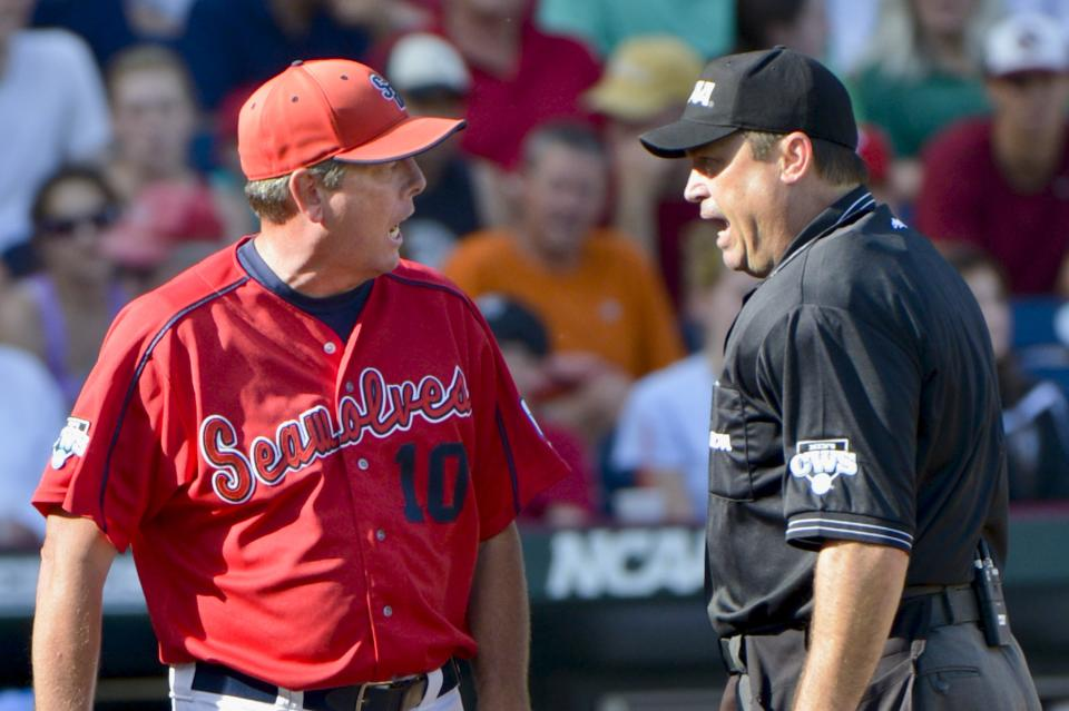 Stony Brook coach Matt Stenk, left, argues with home plate umpire Mark Chapman about whether Stony Brook's Kevin Courtney was safe or tagged out at home plate by UCLA catcher Tyler Heineman, in the fifth inning of an NCAA College World Series baseball game in Omaha, Neb., Friday, June 15, 2012. (AP Photo/Ted Kirk)
