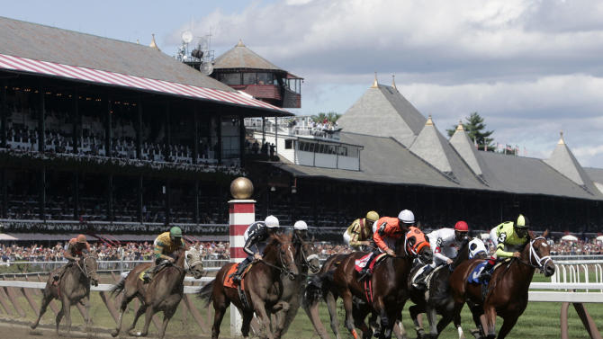 FILE-  In this Aug. 18, 2007 file photo, horses race into through the first turn at Saratoga Race Course in Saratoga Springs, N.Y. Saratoga Springs' racetrack is still going strong as it marks its 150th anniversary this summer, the centerpiece attraction in a town that's also known for mineral springs, Victorian charm and upscale hotels, shops and restaurants. (AP Photo/Mike Groll, File)