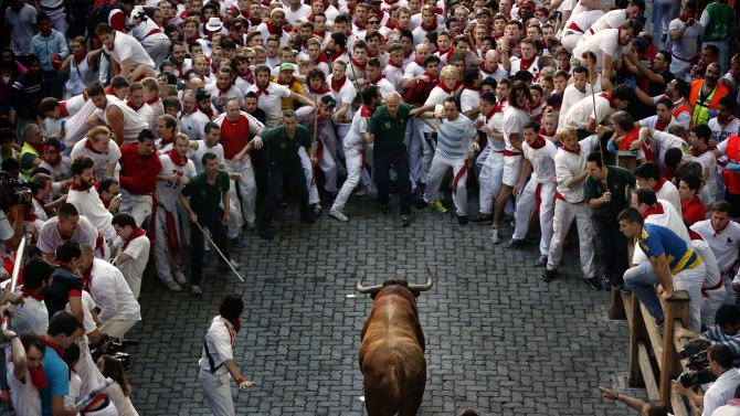 "An Alcurrucen's ranch fighting bull runs towards revelers during the running of the bulls of the San Fermin festival, in Pamplona, Spain, Sunday, July 7, 2013. Revelers from around the world arrive to Pamplona every year to take part on some of the eight days of the running of the bulls glorified by Ernest Hemingway's 1926 novel ""The Sun Also Rises."" (AP Photo/Daniel Ochoa de Olza)"