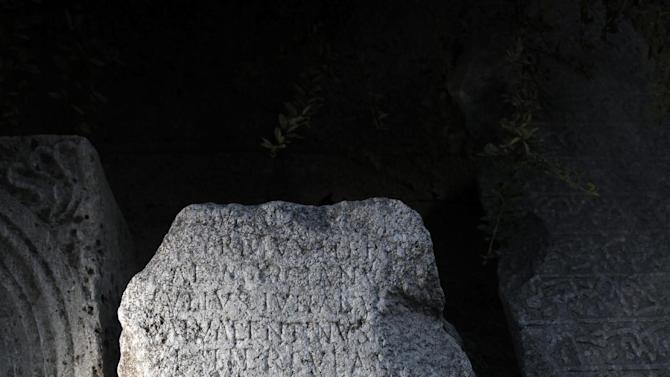 This Friday, Oct. 5, 2012 photo shows ancient Roman inscription on tombstone, found on the site of Ratiaria, an ancient Roman settlement located on the banks of the Danube, in the northwest corner of Bulgaria.  Located on the crossroads of many ancient civilizations, Bulgarian scholars rank their country behind only Italy and Greece in Europe for the numbers of antiquities lying in its soil. But Bulgaria has been powerless to prevent the rape of its ancient sites, depriving the world of part of its cultural legacy and also costing this impoverished Balkan nation much-needed tourism revenue.  (AP Photo/Valentina Petrova)