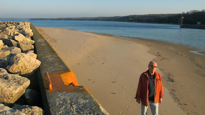 In this Nov. 16, 2012 photo, Jim Simons, who runs a rod and reel repair business in Onekama, Mich., strolls on a sand bar alongside the Portage Lake channel that leads to Lake Michigan at Onekama, Mich.  The sand bar normally would be submerged in water, but low Great Lakes levels have exposed the shoreline in many areas, causing problems for boaters and tourist businesses in small harbor towns. The Great Lakes, the world's biggest freshwater system, are dropping because of drought and climbing temperatures, a trend that accelerated with this year's almost snowless winter and scorching summer. (AP Photo/John Flesher)