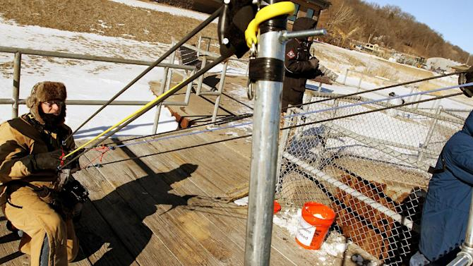 In this Jan. 29, 2014 photo Ken Kester of Clinton, Iowa, uses an oversized homemade slingshot that flings dead fish into the open water for Bald Eagles to to feed on at Lock and Dam 14 on the Mississippi River near Le Claire, Iowa. Kester, who built the contraption, calls it a fish launcher. It can toss a fish a couple hundred feet into the chanel where the water is calmer and eagles feel comfortable snatching up the meals. (AP Photo/The Quad City Times, Kevin E. Schmidt)