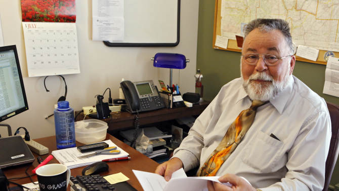 """This July 8, 2014 photo shows William Kistler at work in his office in Denver. Sixty-three-year-old William Kistler views retirement like someone tied to the tracks watching a train coming: It's looming, it's threatening and there's little he can do.""""There is not enough to retire with,"""" said Kistler, a Golden, Colorado, resident who said he is unable to build up a nest egg for his wife with his modest salary helping seniors navigate benefits. """"It's completely frightening to tell you the truth. And I, like a lot of people, try not to think about it too much, which is actually a problem.""""(AP Photo/Ed Andrieski)"""