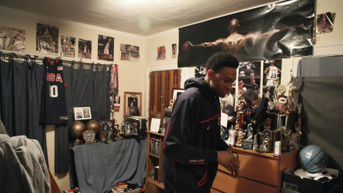 "In this photo taken in Chicago, on Monday, March 12, 2012, Jabari Parker walks around his bedroom preparing to go to a 6:00 a.m. Bible study  in Chicago's Hyde Park neighborhood before school. There's a reminder to ""put the Lord first"" on Jabari's bedroom door along with several sheets of eight-by-10 white paper. One lists the Ten Commandments. Then, there's his ""Always Remember"" list, with his own personal rules that reflect helping and caring for others. (AP Photo/Charles Rex Arbogast)"