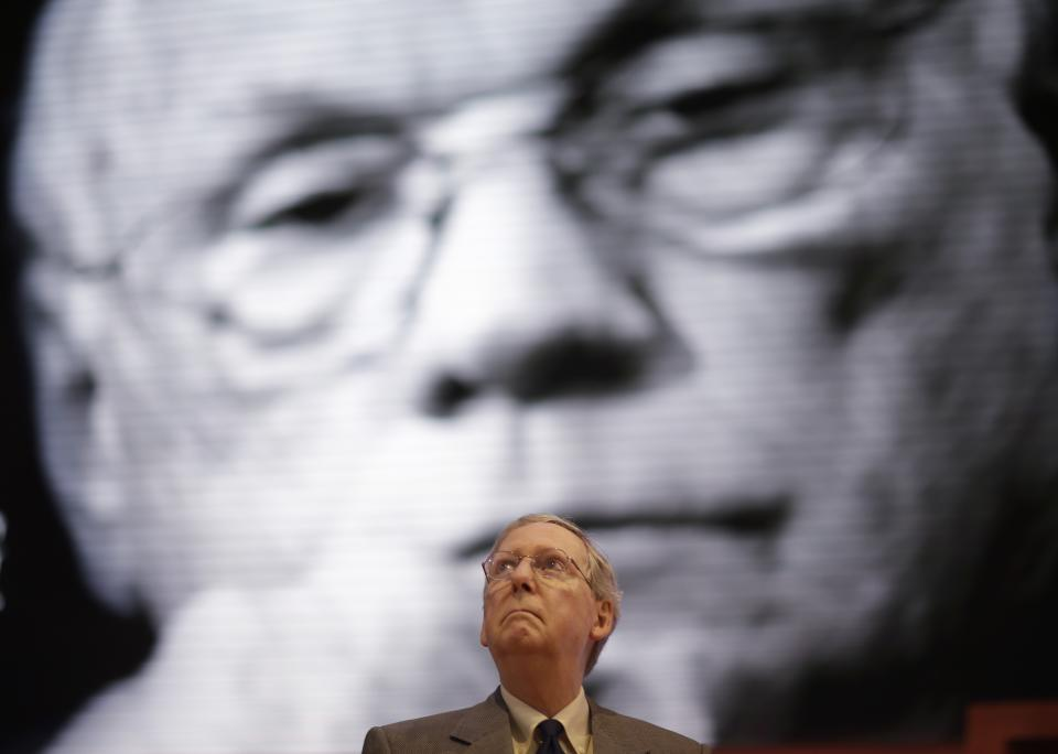 Senate Minority Leader Sen. Mitch McConnell, R-Ky., checks out the stage of the Republican National Convention  in front of a picture display of Neil Armstrong, the first man to walk on the moon, in the Tampa Bay Times Forum in Tampa, Fla., on Sunday, Aug. 26, 2012. (AP Photo/David Goldman)