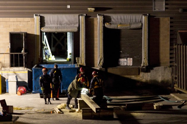 Rescue workers cut timber as attempts continue to secure the building before searching for any survivors at the site of the collapsed roof of the Algo Centre Mall in Elliot Lake, Ontario on Monday Jun