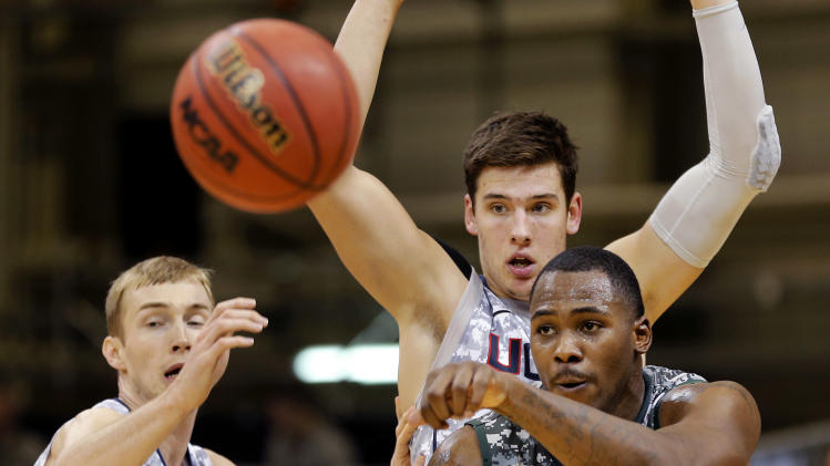Michigan State center Derrick Nix (25) and Connecticut forward Tyler Olander (10), back, watch the ball during their NCAA men's basketball game on Saturday, Nov. 10, 2012, on the Ramstein U.S. Air Force Base, in Ramstein, Germany.  (AP Photo/Michael Probst)