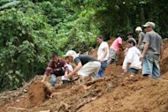 Philippine rescuers claw through dirt in search for survivors a day after a landslide buried workers in mining tunnels in a gold-rich southern Philippines area in Kingking village of Pantukan town, Compostela province. Philippine officials say there is little chance of finding more survivors, with 22 people likely killed in the disaster