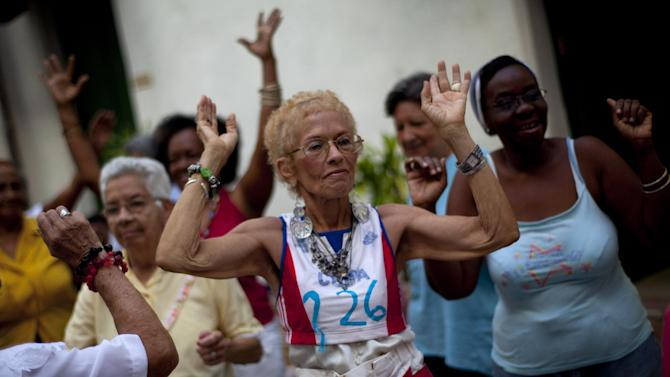 In this picture taken Aug 2, 2012, women dance at a senior center, that provides retirees with medical attention, meals and social activities, in Havana, Cuba. Cuba grapples with having the oldest citizenry in Latin America, a phenomenon fueled by low birth rates and long life expectancies, plus the migration of young people and women. The government has already postponed the retirement age and is trying to create more homes and programs for the elderly, but still will have to handle the economic consequences of its increasingly graying population.(AP Photo/Ramon Espinosa)