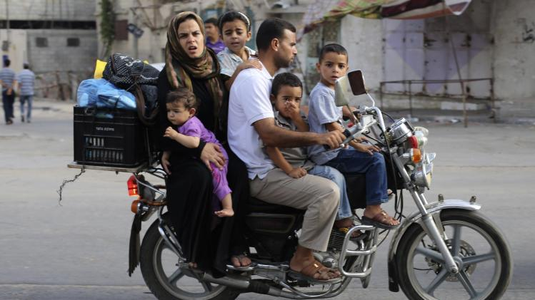 A Palestinian family ride a motorcycle as they flee their house in Khan Younis in the southern Gaza Strip