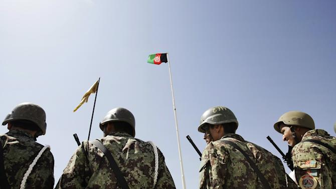Afghanistan's flag is seen, top right, as Afghan soldiers stand attention during a hand over ceremony of U.S.- run prison to Afghan government in Bagram north of Kabul, Afghanistan, Monday, Sept. 10, 2012. U.S. officials handed over formal control of Afghanistan's only large-scale U.S.-run prison to Kabul on Monday, even as disagreements between the two countries over the thousands of Taliban and terror suspects held there marred the transfer. (AP Photo/Musadeq Sadeq)
