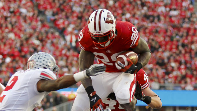 Wisconsin running back Montee Ball (28) leaps over Ohio State's Christian Bryant , left, and Ryan Shazier on a touchdown run during the first half of an NCAA college football game Saturday, Nov. 17, 2012, in Madison, Wis. (AP Photo/Andy Manis)