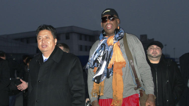 Former NBA basketball star Dennis Rodman walks with Vice Minister of North Korea's Sports Ministry, Son Kwang Ho, as Rodman arrives at the international airport in Pyongyang, North Korea on Thursday, Dec. 19, 2013. (AP Photo/Kim Kwang Hyon)