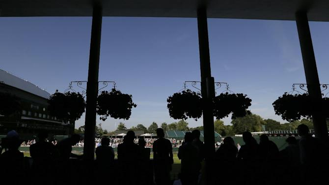 Spectators shelter from the sun under a roof as they watch play on an outside court during the first day of play at the All England Lawn Tennis Championships in Wimbledon, London, Monday June 29, 2015. (AP Photo/Tim Ireland)