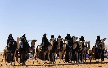 Tuareg men ride camels in the desert during the 19th Ghat Festival of Culture and Tourism, in Ghat