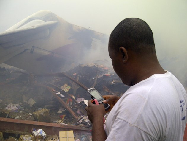 A man using his cell phone stands near the wreckage of a crashed passenger plane in a neighborhood just north of Murtala Muhammed International Airport, in Lagos, Nigeria, Sunday, June 3, 2012. The pa