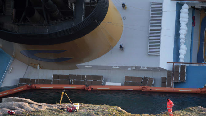 """The cruise ship Costa Concordia lays on its side after running aground off the tiny Tuscan island of Giglio, Italy, Tuesday, Jan. 17, 2012. Italian navy divers on Tuesday exploded holes in the hull of a cruise ship that grounded near a Tuscan island to speed the search for 29 missing passengers and crew while the seas remain relatively calm. The search intensified as prosecutors prepared to question the captain, who is accused of causing the wreck that left at least six dead by making a maneuver that the Italian cruise operator said was """"unapproved and unauthorized."""" (AP Photo/Gregorio Borgia)"""