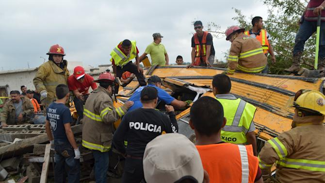 Firefighters inspect the wreckage of a passenger bus after a tornado hit the town of Ciudad Acuna