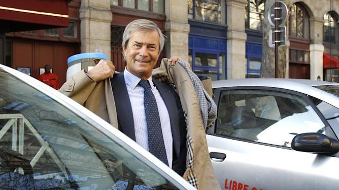Vincent Bollore, CEO of investment group Bollore, stands by Autolib' electric cars during the inauguration of the the Autolib' service in Paris