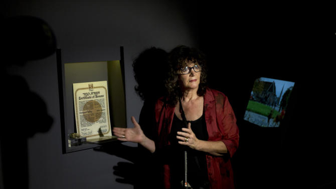 "FILE - In this Monday Sept. 30, 2013 file photo, Irena Steinfeldt, an official at Israel's Yad Vashem Holocaust memorial, shows a certificate recognizing Mohamed Helmy, an Egyptian physician in Berlin, as ""Righteous Among the Nations"" for saving a Jewish family during the Holocaust, in Jerusalem. A member of the family of the first Arab honored by Israel for risking his life to save Jews during the Holocaust says the family isn't interested in the recognition. The Egyptian doctor, Mohamed Helmy, was honored posthumously last month by Israel's Holocaust memorial for hiding Jews in Berlin during the Nazis' genocide, but a family member tracked down by The Associated Press this week in Cairo said her relatives wouldn't accept the award, one of Israel's most prestigious (AP Photo/Sebastian Scheiner, File)"