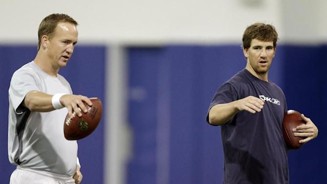 FILE - In this April 11, 2013, file photo, Denver Broncos quarterback Peyton Manning, left, and brother New York Giants quarterback Eli Manning, talk during their football workout at Duke in Durham, N.C. Peyton Manning back in Indianapolis — in a Broncos uniform. Peyton vs. younger brother Eli in another Manning Bowl. The NFL schedule, released Thursday, April 18, 2013, is filled with return visits and intriguing matchups. (AP Photo/Gerry Broome)
