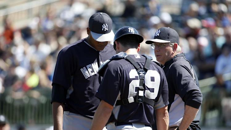 New York Yankees starting pitcher Ivan Nova (47) talks with catcher Francisco Cervelli (29) and pitching coach Larry Rothschild in a spring exhibition baseball game against the Houston Astros, Saturday, March 8, 2014, in Kissimmee, Fla. (AP Photo/Alex Brandon)
