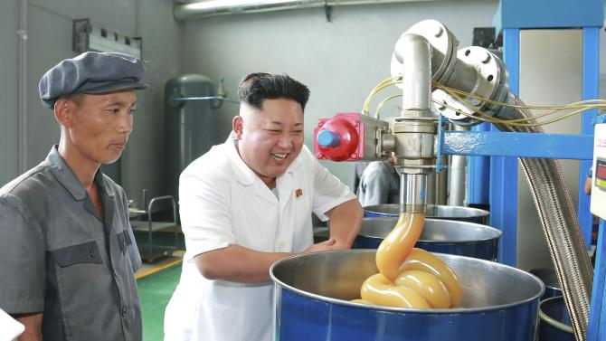 KCNA picture shows North Korean leader Kim Jong Un smiling during a visit to the Chonji Lubricant Factory