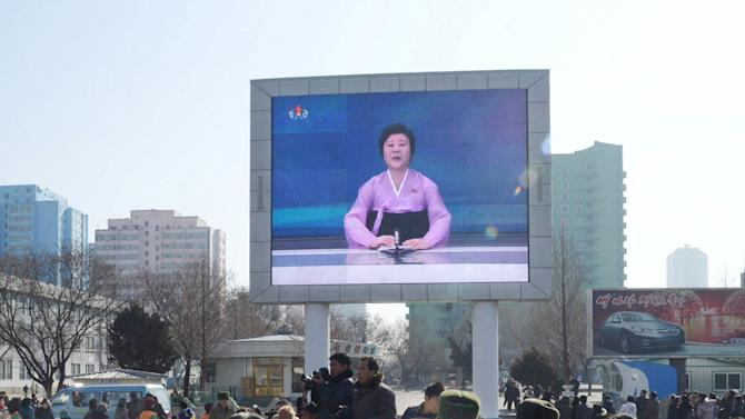 """North Koreans watch a huge screen broadcasting an official announcement that the country """"successfully"""" put an Earth observation satellite into orbit, calling it an """"epoch-making"""" achievement, in Pyongyang"""